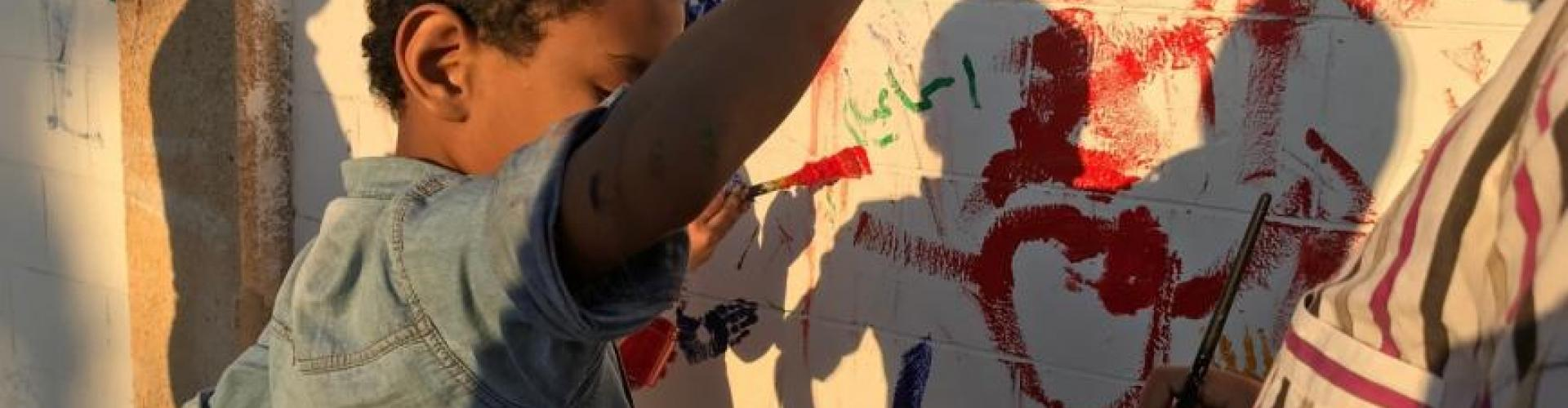 Autistic children in A Global Voice for Autism's Jordan program paint an autism inclusion mural on a wall outside the girls secondary school.