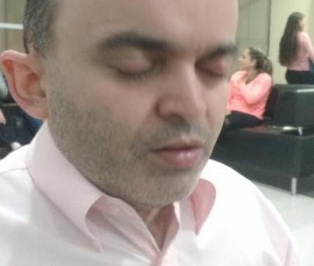 in this picture we can see Alex Garcia, a deafblind Brazilian.  He is with his eyes closed. He has sunglasses on his head, he is wearing a light pink shirt. At the back we can see some people sitting on a sofa. It looks like a hotel/ convention hall