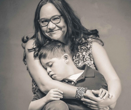 A black and white picture of myself looking into the camera and smiling, while I hug my son Alan, who's lying his head on one of my arms and looking to the side.