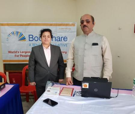 Zainab stands in front of a Bookshare Banner with Dr. Homiyar Mobedji, Bookshare Africa/India Head